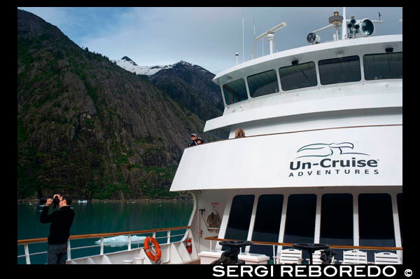 "Passengers on cruise ship Safari Endeavour at anchor at Fords Terror, Endicott Arm, Tongass National Forest, Juneau, Alaska, USA. Cliff-walled fjords sliced into the mountainous mainland are on tap today as you slowly slip into an area widely acclaimed as the most beautiful in Alaska. With more designated Wilderness Areas than any state in the nation, the finest include Endicott Arm and Ford's Terror, a pristine tidal inlet and fjord. Explore this majestic fjord by kayak or skiff, a unique opportunity indeed. View rugged ice-covered mountains gleaming high overhead and a glacier that actively calves into the ice-filled fjord of Endicott Arm. Toast your voyage with a festive Farewell Dinner, and before turning in, your Expedition Leaders share a ""photo journal"" of your trip together."