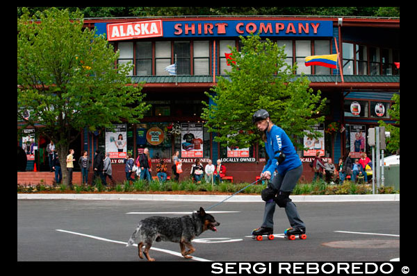 Downtown. Skating with a dog in the streets of Juneau. S Franklin street. Alaska Shirt Company. Alaska, USA.  The City and Borough of Juneau is the capital city of Alaska. It is a unified municipality located on the Gastineau Channel in the Alaskan panhandle, and is the second largest city in the United States by area. Juneau has been the capital of Alaska since 1906, when the government of what was then the District of Alaska was moved from Sitka as dictated by the U.S. Congress in 1900. The municipality unified on July 1, 1970, when the city of Juneau merged with the city of Douglas and the surrounding Greater Juneau Borough to form the current home rule municipality. The area of Juneau is larger than that of Rhode Island and Delaware individually and is almost as large as the two states combined. Downtown Juneau  is nestled at the base of Mount Juneau and across the channel from Douglas Island. As of the 2010 census, the City and Borough had a population of 31,275. In July 2013, the population estimate from the United States Census Bureau was 32,660, making it the second most populous city in Alaska after Anchorage.(Fairbanks is however the second-largest metropolitan area in the state, with more than 97,000 residents.) Between the months of May and September, Juneau's daily population can increase by roughly 6,000 people from visiting cruise ships.