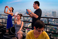 Bangkok. Asian people taking pictures. Banyan Tree Rooftop Vertigo & Moon Bar, Restaurant, , Bangkok , Thailand. View of the city, Vertigo Bar and Restaurant, roof of the Banyan Tree Hotel, at dusk Bangkok, Thailand, Asia. Reaching for the clouds at Vertigo and Moon Bar on the 61st floor of the Banyan Tree hotel is one of the best ways to end a long day in Bangkok. There is no lack of rooftop bars in town but Vertigo has always been amongst the favourites. With an unusual narrow and elongated shape, the entire top of the building is occupied by both the bar and the restaurant and gives the unusual impression of being aboard a spaceship in the sky. Located on Sathorn road, a very large busy avenue peppered with tall glass and metal skyscrapers and not far from the Lumpini park and Silom area, Banyan Tree is a name often associated with luxury.