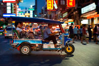 Bangkok. Tuk tuk in the street. View down Thanon Yaowarat road at night in central Chinatown district of Bangkok Thailand. Yaowarat and Phahurat is Bangkok's multicultural district, located west of Silom and southeast of Rattanakosin. Yaowarat Road is the home of Bangkok's sizable Chinese community, while those of Indian ethnicity have congregated around Phahurat Road. By day, Yaowarat doesn't look that much different from any other part of Bangkok, though the neighbourhood feels like a big street market and there are some hidden gems waiting to be explored. But at night, the neon signs blazing with Chinese characters are turned on and crowds from the restaurants spill out onto the streets, turning the area into a miniature Hong Kong (minus the skyscrapers).