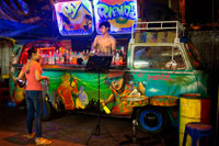 Bangkok. A VW Volkswagen bus cocktail bar in Soi Rambuttri. Bangkok. Grab a beer with ice or a cocktail from one of the pop-up bars and pull up a seat with the locals. The best place to try is along the back of the temple where you can hear some great live music and a friendly and cheerful atmosphere. These places don't tend to get busy until after 23:00 though. You can also find a couple of the amazing decorated car bars on Rambuttri – a VW campervan and a songtaew. VW bars are converted vans with staff operating the cocktail shakers from inside the Volkswagen. Decorated with neon fairy lights, disco balls and impressive sound systems blaring out the latest pop hits, they're a noticeable addition to Bangkok party street Sukhumvit 11.