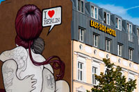 I love Berlin. East Side Hotel in front of East Side Gallery. The East Side Gallery is a 1.3 km-long painted stretch of the former Berlin Wall along the Mühlenstrasse in former East Berlin. It is the largest open-air gallery in the world with over one hundred original mural paintings. Galvanised by the extraordinary events which were changing the world, artists from all around the globe rushed to Berlin after the fall of the Wall, leaving a visual testimony of the joy and spirit of liberation which erupted at the time.   Wall murals had previously been a highlight for visitors and a Berlin attraction for years but were only to be found on the western side of the Wall. The artists transformed the grey concrete rearticulating this into a lasting expression of freedom and reconciliation.