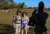 "A couple of tourists photographing with zebras in background done walking safari camp near the Eagle Island Camp by Orient Express , outside the Moremi Game Reserve in Botswana . After scanning the horizon , Botsualo , our guide , you authorize us to set down tents and start a walk at sunset. "" No need to worry , in this area there are no predators delta "" he says when he sees our faces , among frightened and hopeful to walk through that area . Normally in parks but you can not walk in certain areas , guided self . This is a . Stealthy footsteps move huge recognizing droppings of elephants and monkeys , to a pasture area where several groups of zebra, wildebeest and antelope roam free . We discovered a skeleton giraffe. Further away , next to a huge baobab a rogue elephant . We can not approach too but being there, without the protection of the car, in nature, in his field , is a wonderful and liberating feeling equally. As the sun goes down we retired . Although it is the best time to observe the animals have to go back to camp, make a fire and cook dinner"