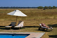 A tourist sunbathes in a swimsuit poolside at Camp Khwai River Lodge by Orient Express in Botswana , within the Moremi Game Reserve Wild . Khwai River Lodge is situated on the banks of the Khwai River , adjacent to the Moremi Game Reserve and the Okavango Delta outside . On its banks and wetlands inhabited by numerous species, hippos , elephants , lions , leopards , antelopes and abundant species of birds - just a few meters from the camps , open laterally through the dining room and from the lawn overlooking the pool. The camp has 15 luxury tents magnificent , suite with copper bath Victorian style outdoor shower, private pool and a secluded terrace. Each store has a shaded area with a hammock and comfortable chairs overlooking the Khwai River and its abundant wildlife . Equipped with all modern amenities , including mini -bar and ventilation - air conditioning shops were decorated by the famous designer Graham Viney