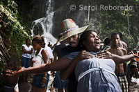 "A couple of Haitians by the waterfall of Saut d'eau. Haitian Voodoo officiants are simplicity in dress and attributes that attach to it as a clear religious reference. Not so among his descendants who hold similar hierarchies in those notes, however, an overload in the visible elements. So are multiple types of seed bead necklaces which are made with those sold in some public places. These insert other objects such as plates and key chains called ""tears"" of crystal chandeliers. In a note collar dozens of spools of sewing threads of different colors. It is clear that the cultural function added decorative elements. Not lacking in these attributes gold medals with pictures of St. Barbara or the Virgin of Caridad del Cobre."