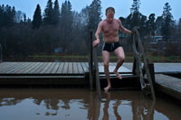 A man cools outside the private Sauna Pikkukoski north of the city of Helsinki, Vanhankaupunginselkä lakeside, near the town of Oulunkylä Aggelby. A defined area of the lake has heating in water so that it never freezes in winter and people can swim.