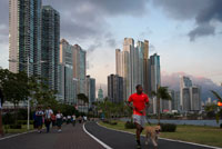 Man running with dog in Balboa Avenue skyline skyscraper road seawall new. Skyline, Panama City, Panama, Central America. Cinta Costera Pacific Ocean Coastal Beltway Bahia de Panama linear park seawall skyline skyscraper modern. Coastal Beltway (Cinta Costera), Panama City, Panama. Panama City is one city in Central America where congestion has reached crisis point. The city is going through an unprecedented period of stability and investment and there are ample public funds for infrastructure improvement projects.