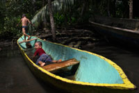 Kids play in one of the local boats used by the Ngobe Indians as their main form of transport, sheltered under a makeshift lean-to. Channel to entrance at The Ngobe Bugle Indian Village Of Salt Creek Near Bocas Del Toro Panama. Salt Creek (in Spanish: Quebrada Sal) is a Ngöbe Buglé village located on the southeastern end of Bastimentos island, in the Bocas del Toro Archipelago, Province and District of Panama.