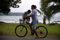 "Mother with his kid in a bicycle. Bocas del Toro, Panama. Bocas del Toro (meaning ""Mouth of the Bull"") is a province of Panama. Its area is 4,643.9 square kilometers, comprising the mainland and nine main islands. The province consists of the Bocas del Toro Archipelago, Bahía Almirante (Almirante Bay), Laguna de Chiriquí (Chiriquí Lagoon), and adjacent mainland. The capital is the city of Bocas del Toro (or Bocas Town) on Isla Colón (Colón Island). Other major cities or towns include Almirante and Changuinola. The province has a population of 125,461 as of 2010."