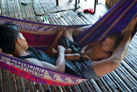Men and his child doing a siesta in a  hammock in the village of the Native Indian Embera Tribe, Embera Village, Panama. Panama Embera people Indian Village Indigenous Indio indios natives Native americans locals local Parque National Chagres. Embera Drua. Embera Drua is located on the Upper Chagres River. A dam built on the river in 1924 produced Lake Alajuela, the main water supply to the Panama Canal. The village is four miles upriver from the lake, and encircled by a 129.000 hectare National Park of primary tropical rainforest.