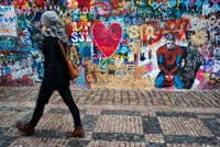A girl walks past the John Lennon Wall in Prague center. The John Lennon Wall is a wall, which once was one most of which could be found in any of the buildings in the Mala Strana district in the capital of the Czech Republic: Prague, but since the beginning of the 80 so named to be continually decorated with graffiti-inspired new figure of John Lennon and pieces of Beatles songs. The wall is located in the Plaza Velkop? Evorské nám? Stí, against Buquoy Palace which houses the French embassy and is owned by the Knights of the Maltese Cross Order that allow continuously follow new graffiti painting on it.
