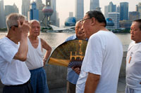 China, Shanghai, morning tai chi exercise on The Bund. Shanghi Bund : Early morning tai chi exercises with swords on the Bund in Shanghai China. The best taichi lessons I've had were from an old guy who practiced outside at 7am every morning. I learned 4 excellent techniques that I still use in my MMA training on a regular basis- a method of catching a kick and throwing your opponent, redirecting a straight punch and countering in the same motion, countering double underhooks with a throw, and escaping a shoulder lock while setting up your own.  It's a really fascinating martial art because every one of those dance like movements represents a simple practical fighting technique or strategy, but it's hard to see how the movements translate into combat applications without a master of the art demonstrating it. But either way even without a kungfu master, the forms themselves are great low impact exercise that you can find everywhere in the city for free every morning.