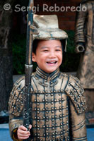 A boy disguised in a suit that mimics the Warriors in Xian Bingmayong archaeological zone, located 35 miles east of the city. The discovery of these warriors, like most archaeological discoveries occurred by chance. It was the spring of 1974, peasants digging a well near Mount Li, when, suddenly, they found fragments of the terracotta statues.